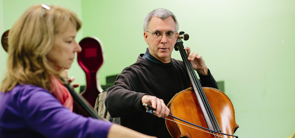Cello instructor Steven Wiggs demonstrates a phrase for a Bridges student